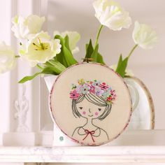 A darling project for hoop embroidery by hand. A pretty girl wears flowers in her hair and her pink cheeks seem warmed by the sun, designed by Kirsty Neale.