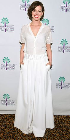 Anne Hathaway keeps a flowy and all-white outfit elegant with a delicate gold necklace and a red lip.