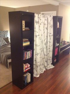 My room divider - two Ikea bookshelves (EXPEDIT - $60/each), a tension rod, and two curtain panels (also from Ikea). PERFECT for my space!