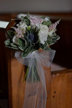 Tied pew end of ivory roses, blue thistles, white freesia,  lisianthus and pink astilbe with foliage and tulle bow.