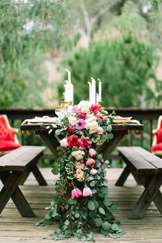 A bountiful floral table runner and candles dress up a casual picnic table