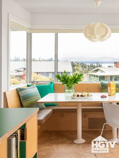 This modern breakfast nook was decorated 1960s style. It features green throw pillows, a retro hanging pendant and white chairs. See more on HGTV.com.