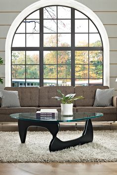 Noguchi coffee table on shag rug in front of modern tufted sofa and arched picture window