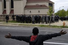 A protestor gestures before riot police on April 27, 2015 in Baltimore, Maryland on April 27, 2015 in Baltimore, Md. (Photo by Brendan Smialowski/AFP/Getty)