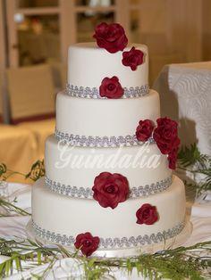 Tarta de boda en fondant con detalle de rosas granates.