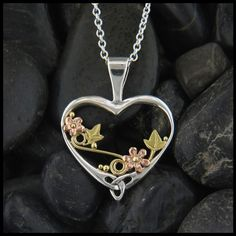 Feminine heart pendant in Gold and Silver with ivy and daisy flower details.