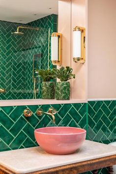 Emerald green metro tiles, pink ceramic sinks, marble topped antique barley twist leg table, brass bathroom lighting and fixtures. #BathroomLighting