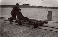Happy Throw Back Thursday! Wheeled Trolley on the Pier, M. Smith and B. Daniels play with the freight trolley on the pier. The Pioneer Cemetery is in the background, identified by the grove of trees. Cemetery, Thursday, Trees, Play, History, Happy, Vintage, Collection, Arbor Tree