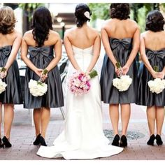 Bride and bridesmaids: bouquets from behind. (Photographer unknown)