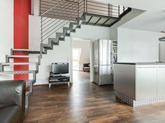 Nichts stellt sich Licht das die großen Fensterflächen in das Apartment bringen in den Weg. Die Treppe im Industrielook harmoniert mit der freistehenden Küche.