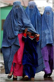 Wearing a burqa for the first time | Three Afghan women walked together in Kabul, Afghanistan's capital, with a little girl, who hid herself from rain under her mother's burka.