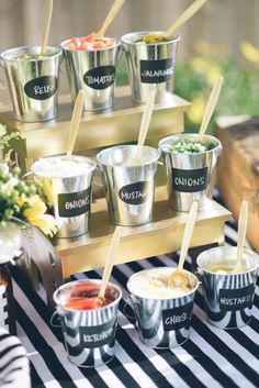 Create a Cute Condiment Display: Go beyond basic ketchup and mustard by offering more unique options for hot dog and hamburger toppings, then display them in individual labeled buckets. Click through to find more fun summer party ideas for your next backyard BBQ party.