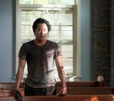"""Glenn (Steven Yeun) looks for a Bible Glock in """"No Way Out""""."""