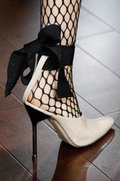 Fishnet hose take on a demure look in with bowtie shoes.  WorkingLook.com