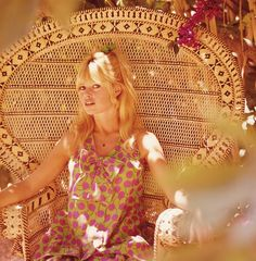 """Bridgette Bardot in the 1970's sitting on a rattan """"peacock"""" chair."""