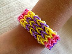 Rainbow Loom bracelet made from rubber bands, patterned bracelet in yellow, purple, and pink.