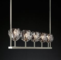 "RH Modern's Boule De Cristal Linear Chandelier 48"":Crafted of solid brass and crystal, lighting designer Jonathan Browning's sculptural fixture is a testament to his passion for luxe materials and handcraftsmanship. Evoking the minimalist spirit of 1960s design, each faceted sphere is ground and polished by hand to reflect and refract the light."