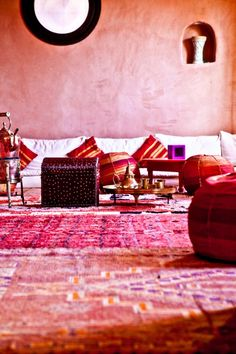 Check out Atlas Kasbah in Agadir Morocco. Love the hot colored carpets & tadelakt walls with the low Moroccan banquettes.
