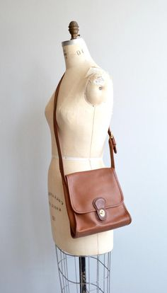 Vintage 1980s Coach Shelburn Flap in classic British tan leather with interesting shape, flap closure, roomy interior and long adjustable crossbody strap. --- M E A S U R E M E N T S --- 9 x 9 3 wide base 37 long strap maker/brand: Coach   serial No. 9038 condition: excellent ➸ More vintage bags http://www.etsy.com/shop/DearGolden?section_id=10308208 ➸ Visit the shop http://www.DearGolden.etsy.com _____________________ ➸ instagram   deargolden ➸ tw...