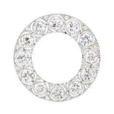 Platinum and Diamond Circle Pin, J. E. Caldwell & Co. Set continuously with 10 old European-cut diamonds ~4.20 cts., accented by pairs of single-cut diamonds, circa 1910.
