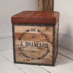 A very robust storage seat this tea chest box has a steel frame reclaimed hand printed hardwood boards and a tufted leather upholstered removable