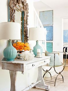 Console Style  { whitewashed wood w/ rough turq lamps; mirror as art; 3 tone canvas' on stair landing; coral, punch of color & mixed metals, GORGEOUS ENTRY (drooling) }