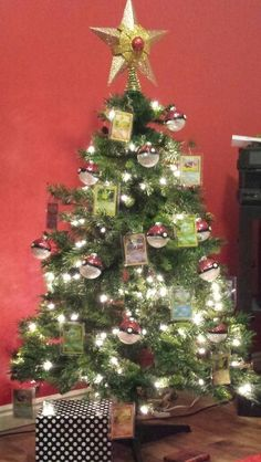 Pokemon Christmas tree with a Staryu in place of a star topper, glitter pokeball ornaments, and hanging Pokemon cards - Pikachu, Mew, Eevee, Squirtle, Charmander, and Bulbasaur.