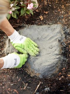 Step 5 to Garden Pathway  Fill the hole evenly with concrete. Use your hands to press and sculpt the concrete into a leaf shape