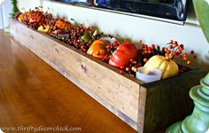 Fill a wood trough with faux pumpkins and bittersweet--a great way to add rustic autumn charm.