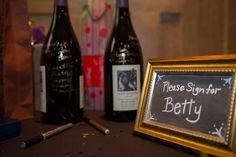 Fun idea for a Birthday: buy a couple of magnum bottles of wine and some gold and silver pens.  Ask guests to write messages to the Birthday person on the wine bottles.  Photo by norastratton.com ; Directions for framed chalkboard sign here: lovepaperpaint.com
