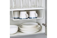 """Hang Baskets to Store Mugs- Kicking things off with a major """"duh."""" How have we wasted this between-shelves space all these years? Read more: 8 Space-Saving Tricks For Tiny Kitchens"""