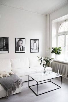 Monochrome living space with a white sofa, and framed photography