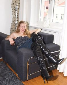 Blonde amateur in jeans and black OTK boots seated in chair