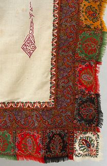 Signed, hand-embroidered jacquard shawl, 1860s. The brilliant multi-colored shawl features a cream colored wool ground signed in two places. Both signatures show when it is folded on the diagonal. The patterned jacquard borders are hand stitched to the ground. They are edged with delicate hand embroidery along the ground as well as hand-embroidered, fringed gates on the outer edge. The borders are reversed from front to back on two sides so that all borders appear the same when the shawl is…