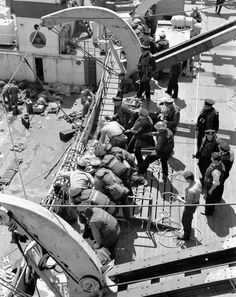 A wounded Royal Navy Beach Commando being taken aboard H.M.C.S. PRINCE DAVID off the Normandy beachhead, 6 June 1944. Photographer: Donovan Thorndick