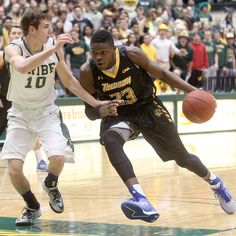 William & Mary's Connor Burchfield tries to keep Towson's Mike Morsell from driving to the basket during the first half Wednesday at W&M. (Photo by Rob Ostermaier / Daily Press)