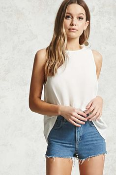 A woven top featuring a round neck, sleeveless cut, a button keyhole back, and a swing silhouette.