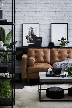 modern interior with white brick walls black elements and a tan leather sofa - loving how the white cowhide rug looks against the dark wood floor