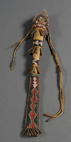 Southwest Beaded Hide Awl Case, Apache, c. last quarter 19th century, beaded with multicolored geometric designs, with rows of tin cones and traces of red and yellow pigment, (missing some cones), lg. 13 1/2 in.   Provenance: Estate of Ed McAndrews