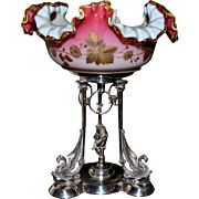Brides Basket: Mt. Washington Hand Blown Victorian Ruffled and Folded Case Glass Brides Bowl With Floral Enamel Decor on Reed and Barton SP Basket/Centerpiece with Cherub, Swinging Birds and Griffin.