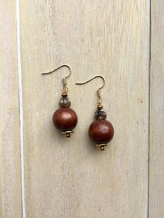 Gold colored dangle earrings with brown wooden beads and Tibetan Agate