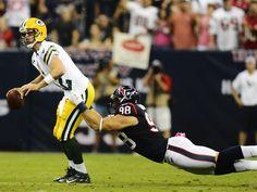 Quarterback Aaron Rodgers trägt für das NFL-Spiel der Green Bay Packers nicht nur die Verantwortung, sondern muss sich obendrein ganz schön abschleppen. An ihm dran hängt Connor Barwin von den Houston Texans.  Doch Rodgers lässt sich von der Anhänglichkeit der Gastgeber nicht ablenken und führt sein Team mit überragenden sechs Touchdownpässen zu einem 42:24-Auswärtssieg. (Foto: Larry W. Smith/dpa)