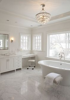 Modern, marble bathroom adds a touch of glam with bling chandelier