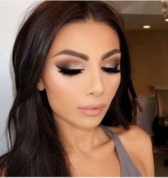 Evening make up look with thick false eyelashes and winged eyeliner. The heavy shaped eyebrows add to the evening look with a touch of glitter in the eyeshadow