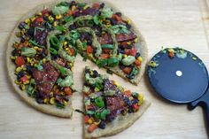 Vegan BBQ Pizza with beans, corn, peppers, and cilantro avocado cream on a homemade whole wheat flax crust