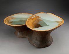 Subterranean Coffee Table by Aaron Laux. This coffee table is made from reclaimed box elder wood and sand blasted glass. The multiple layers of glass descending into the vessel form are the focal point of this design. This table has adjustable feet allowing for the table to be leveled. To clean use a feather duster and a damp cloth.