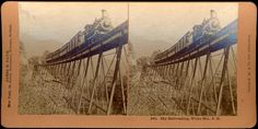 Stereo images of a train on a trestle.