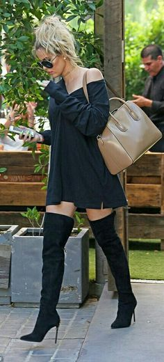 Walking the street with all black thigh high boots (otk boots) and a oversized black long sleeve tshirt top.