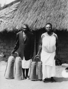 Photographe Jos Gansemans  Lieu de production République démocratique du Congo > Katanga > Lualaba  Culture Lunda  Légende Mwadi Muteb, responsable de la sépulture des empereurs Lunda, avec son mari et les doubles cloches lubemb, un des emblèmes de Mwaant Yaav.