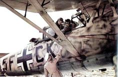 A Deutsches Afrikakorps officer exchanging perhaps a message (the aircraft's strut mask the type of object) with the pilot of a Luftwaffe's observation plane Henschel Hs 126B of 2.(H)/14. The Hs 126 remained in service in North Africa until August 1942